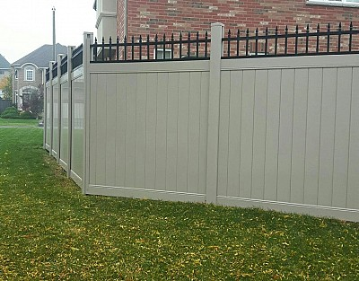 Tan, 7' high privacy fence with black metal picket top